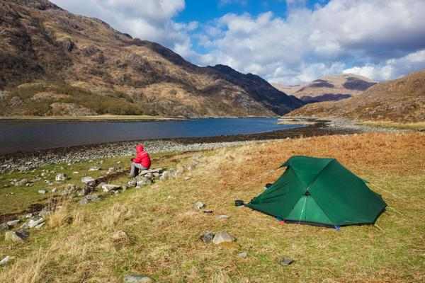 A hiker camping at Barrisdale Bay beside Loch Hourn in the Highlands