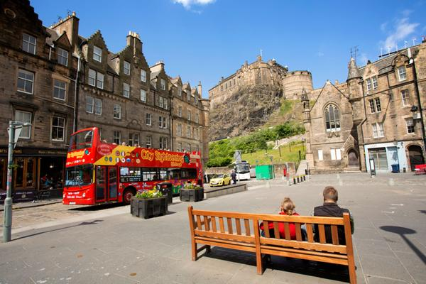 A City Sightseeing bus travelling through the Grassmarket with Edinburgh Castle in the background
