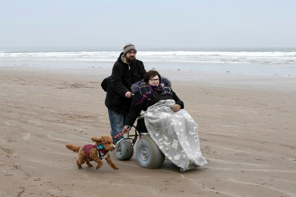 A lady in a wheelchair accompanied by her partner and dog enjoy an amble along a sandy beach