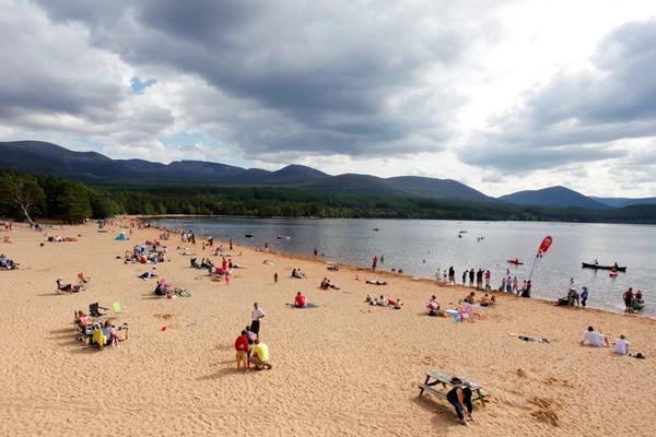Looking across a busy beach by Loch Morlich, a hotspot for watersport activities, in the Cairngorms, Highlands
