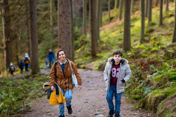 A mum and her son walking along a gravel path through a forest with other walkers in the background
