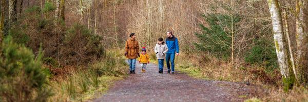 A family walking along a gravel path with a wood behind them