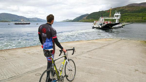 A cyclist looking out at the Corran ferry at Ardgour