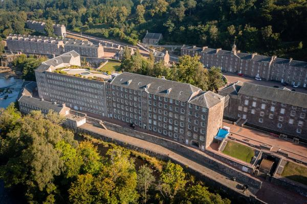 An aerial shot of the buildings and trees of New Lanark