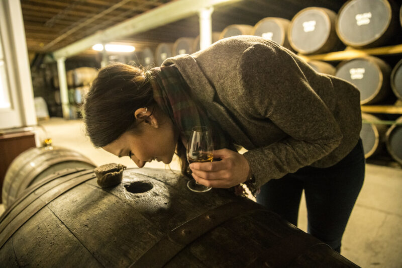 Glen Ord The Nearest Distillery To Inverness Loch Ness In The Highlands Of Scotland  Young Woman Smelling Whisky Through A Hole In An Oak Barrel