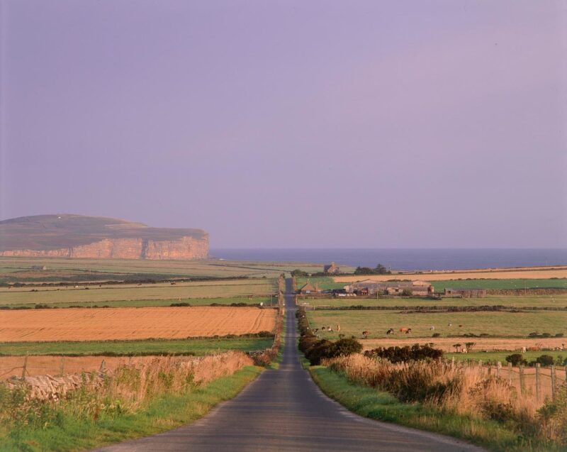 Looking Down A Straight Road Through Farmland With A View To Dunnet Head