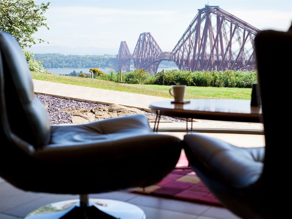 Two leather chairs and a coffee table in the forground, with views to the Forth Bridge beyond