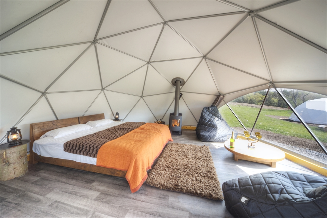 A dome interior, complete with bed, beanbags and wood burning stove