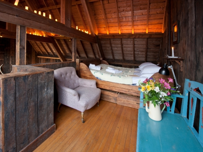 A candlelit mezzanine bedroom in a wooden lodge