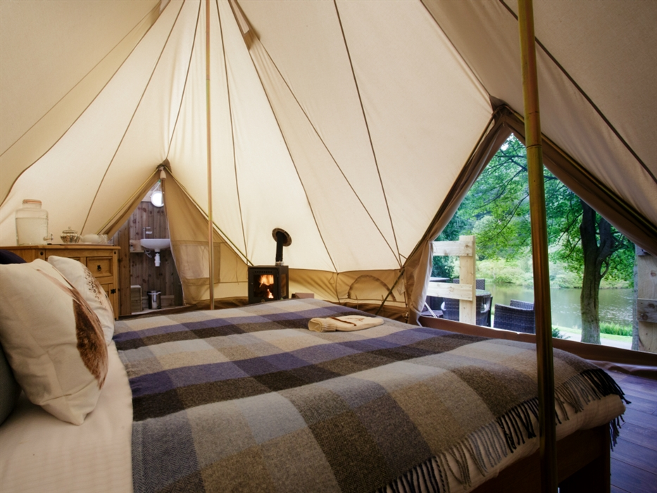 Interior of a canvas tent, complete with bed, log fire and ensuite, as well as view to woodland and pond through open door