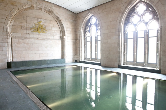 Light shines through abbey windows onto pool below