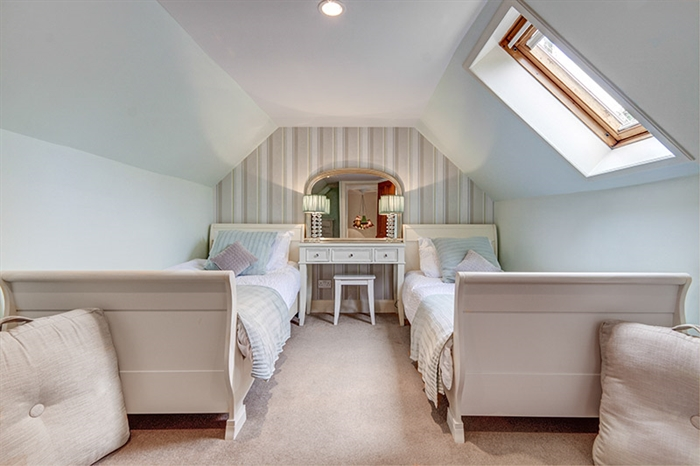 An airy double bedroom with feature wall and dressing table
