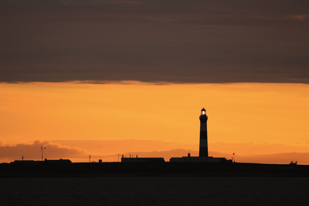 A sillhouette of the lighthouse against the sunrise