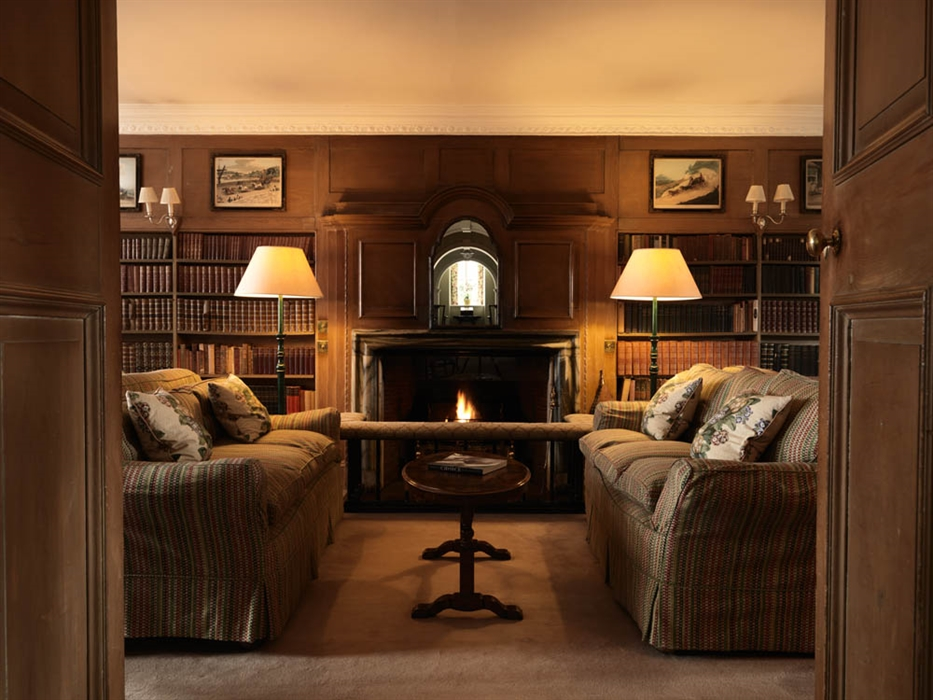 Looking through doors to a cosy lounge with sofes, soft lighting a roaring fire and booklined walls