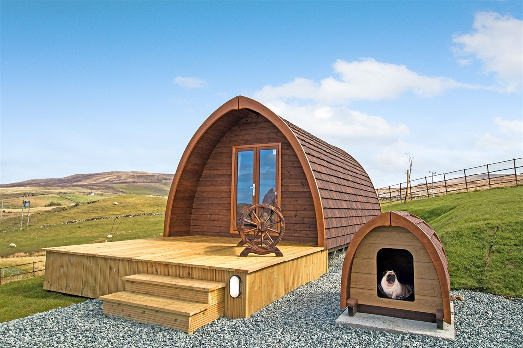 Exterior of wooden camping pod, with mini pod adjacent and housing a pug