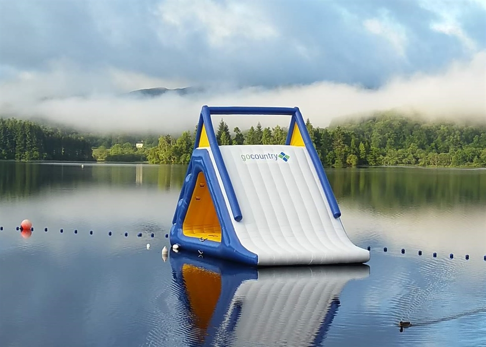 A giant inflatable slideon a loch, with forests beyond