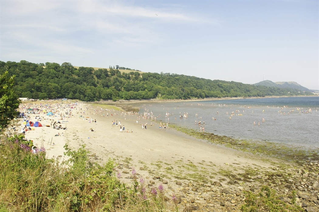 Silver Sands Beach On A Sunny Summer Day With Hundreds Of People Tered Across The Pale Golden Sand Sunbathing And Playing In Water Green H