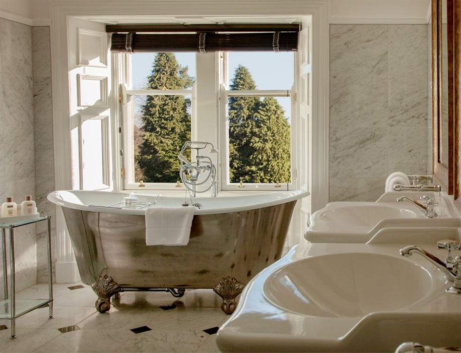 A marbled bathroom featuring rolltop bath, double sink and woodland views